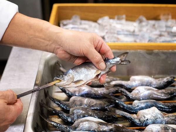 名物の山女魚の塩焼き。一本いっぽん丁寧に串にさしていきます。