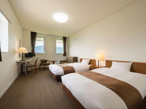 【洋室ツインルーム】窓の外には大自然。清潔で大きなベッドでゆったりとした時間をお過ごしください。