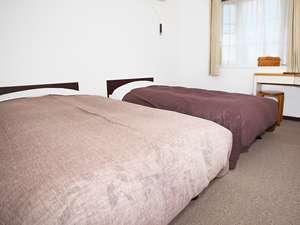 落ち着いた色合いの絨毯と漆喰壁の部屋
