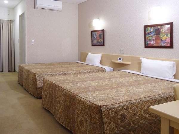 約25㎡の広い部屋に、幅1.5m以上の大型ベッド2台。1名~親子4人まで宿泊可。全室無料ネット接続可