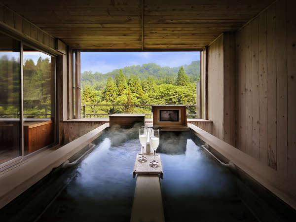【半露天寝湯付和室】寝湯の大きな窓から四季の移り変わりを感じることができます。