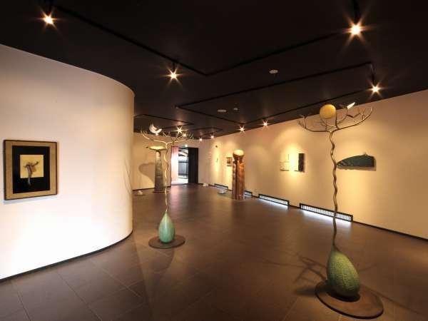 玄関からつながるギャラリーは山形県出身「松田重仁」の彫刻作品が並び日常を忘れる空間