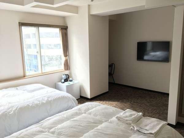 ツインルーム。40インチの壁掛けテレビ、こだわりのシモンズ製ベッドでゆっくりお休み出来ます。