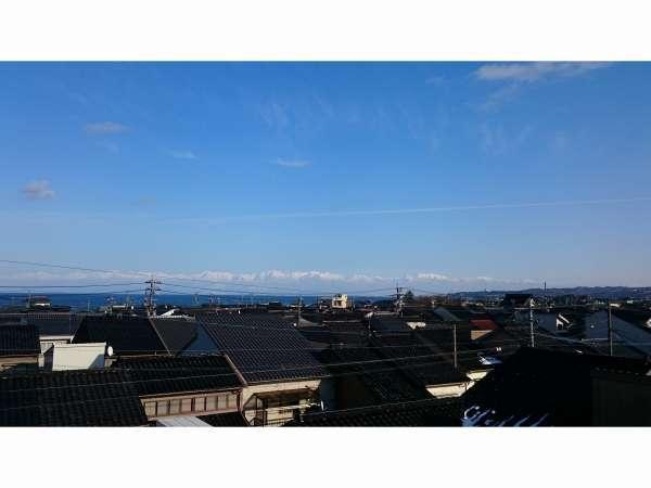 氷見ならではの黒瓦の家波と立山連峰信貴館屋上からの風景