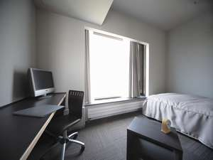 大きな窓から陽光の差し込むシングルルーム