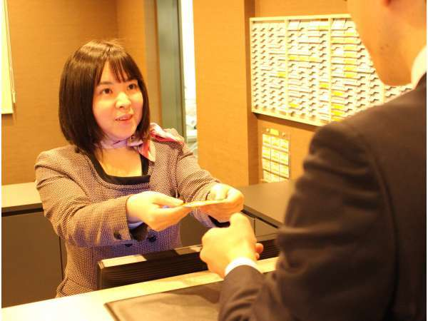 フロントでの接客シーン。笑顔で丁寧な接客を心がけております。