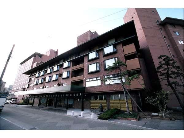 湯の川観光ホテル祥苑の外観。目の前には「松倉川」の清流が流れております。