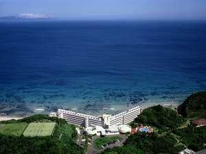 ホテル全景の航空写真です。青い海と白い砂浜、緑の木々に囲まれております。