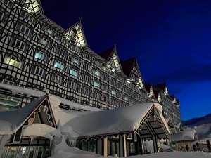 暗闇に沈んでいく白銀の世界の中にホテルグリーンプラザ白馬の美しい夜外観が浮きあがります。