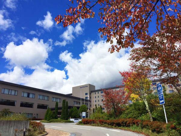 秋晴れの空に映える紅葉とホテル外観
