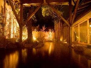 箱根の木々を照らす夜の露天風呂。(男性)