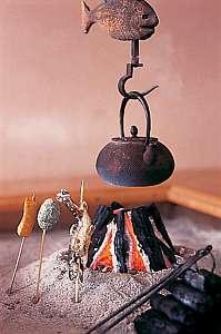 焼き立てのアツアツををそのまま食せる、囲炉裏で焼いた岩魚等。囲炉裏を囲む様にテーブル席もございます。