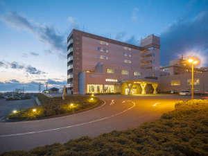 夕暮れ時の外観。日本海に沈む夕日をバッグに佇むホテルです。