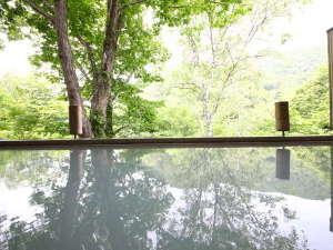 白い温泉が鏡のように景色を映し出す