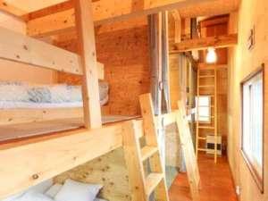 木のぬくもりに囲まれたスペース充分なベッドと横にはスーツケースも置けるスペースを設置