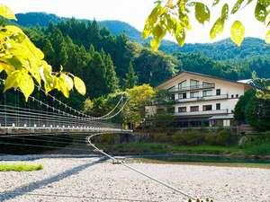 『やまゆりと吊り橋』川のそばに立つ山小屋風の建物です