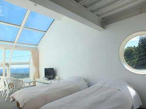 客室、DXツイン。白を基調として、展望風呂と大きな天窓付き。
