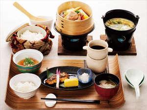 和朝食。季節野菜の蒸籠蒸し、釧路近海で獲れた焼き魚など。白米・玄米・玄米粥から選択できます。