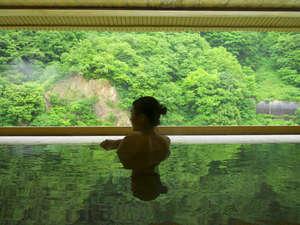 緑に溶けてしまいそうな檜露天風呂「華の湯」。渓谷の景色をひとり占め…。
