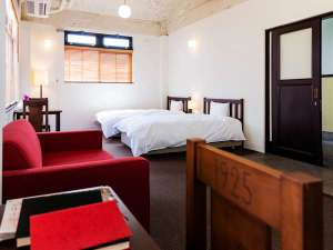 【スタンダード(3名定員)・103】木の優しい色合いと赤いソファがレトロな印象のお部屋。