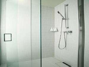 清潔感を感じさせる白いタイルと鏡面を基調にしたシャワーブースタイプのバスルーム