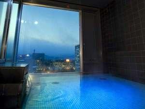 目の前にはきらめく夜景が広がる、最上階大浴場露天風呂。(女性)