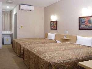 約25㎡の広さに幅1.5m超の大型ベッド2台。1名~親子4人まで宿泊可。全室無料ネット接続可。