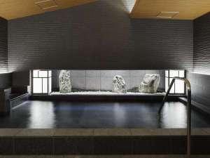 大浴場は黒御影石と坪庭、瓦をイメージしたタイルで構成された静かで落ち着きのある空間。