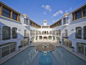 シンメトリーな建物の構図が水面に移り込む、昼下がりのパティオ。抜けるような青空と水面のきらめき。