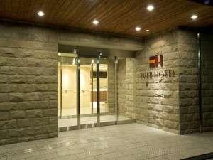 割肌みかげ石の外壁と温かみある光の空間がお客様をお迎えするホテル玄関
