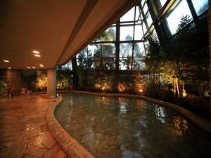 [四季の湯]開放的な吹き抜け、壁面のガラス窓からの景観は夜間照明でさらに幻想的。