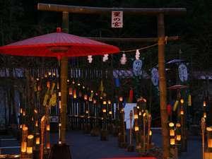 夏の夜の温泉街を竹灯ろうが照ら...