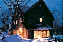 白い雪に温かい光が注がれる冬の外観