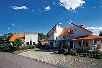 青い空と深緑に映えるオレンジ色の屋根と白い壁が目印
