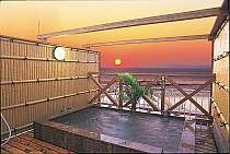 屋上貸切露天風呂(普賢の湯)赤御影石の浴槽から見る夕日は格別!無料で何度でも利用できる。