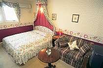 キングサイズベッド。赤の花柄を基調にした可愛らしい部屋
