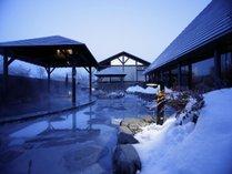 【彩光の湯・露天岩風呂】冬は雪化粧に包まれ、夕暮れ時は趣溢れるムードに。