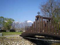 *【ビレッジの景色】橋を渡った先に宿泊棟が。小川も流れるのどかな風景!奥には常念岳ものぞめます!
