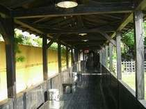 【母屋露天風呂】大浴場へ続く渡り廊下。右手に滝を眺めながらどうぞ