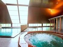 明るい自然光が入り、高い天井が開放的な大浴場。