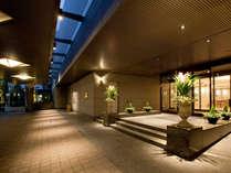 温かなベネツィアングラスシャンデリアの灯が、ゲストを優しく迎えるホテルファサード(玄関)