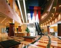 清潔感のあるロビー。館内には24時間営業のコンビニやフィットネスジムなど施設が充実。吹き抜けで開放的。