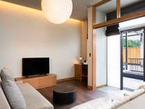 窓越しの無垢素材デスクに大きな2つのソファ。緑を眺めながら創造性を掻き立てるワーケーション