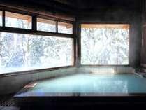 【丸太造りの天然温泉】スキーで疲れた後は雪見風呂でほっこりと。広めの窓から雪景色が眺められる
