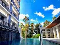 2階プールの入り口から見た風景。透き通る青空とヤシの木で南国リゾートを味わえます。