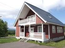 べにがら色に白い窓枠が特徴的な三角屋根の外観
