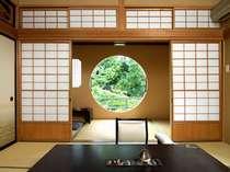 離れ特別室 月見亭二階「二人静」。丸窓から望む木々と差し込む柔らかな日差しに癒されます。