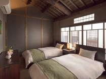小屋裏と丸太梁が広がる寝室。町家の歴史を感じながら快適にお休み頂けます。