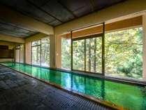 グリーンの浴槽が反射する「名物オリンピック風呂」