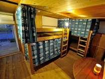 男女混合ドミトリールーム(相部屋)です。各ベッド、岩川旗店さんに製作いただいたカーテンを設置。
